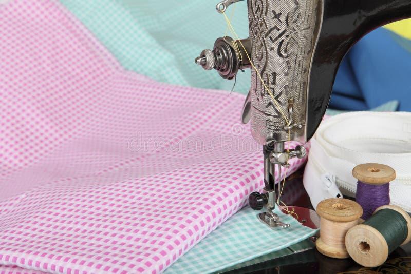 Een deel van een oude naaimachine met een poot, een naald, retro spoelen van draad en stukken van gekleurde stof Achtergrond voor royalty-vrije stock afbeeldingen