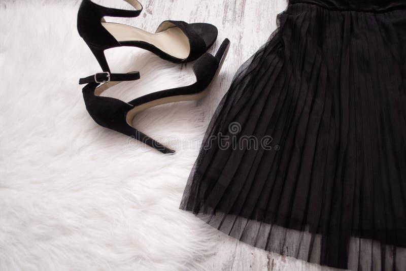 Een deel van een zwarte geplooide rok en zwarte schoenen Het concept van de manier Close-up royalty-vrije stock afbeelding