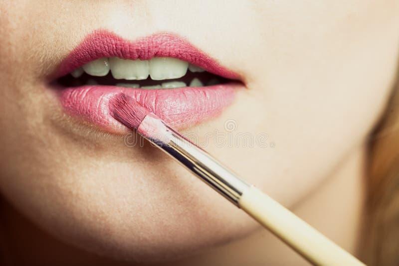 Een deel van gezicht Vrouw die roze lippenstift met borstel toepassen royalty-vrije stock foto's