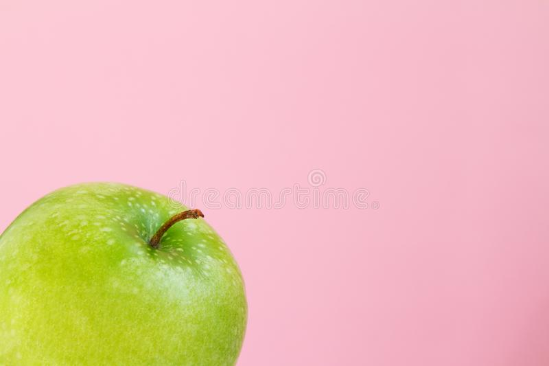 Een deel van groen Apple op roze achtergrond stock foto