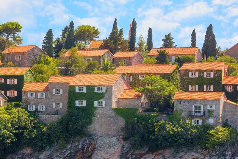 Een deel van het Eiland Sveti Stefan in Budva, close-up met hemel en wolken montenegro royalty-vrije stock afbeeldingen