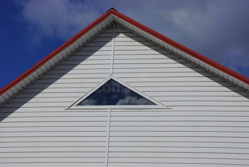 Een deel van het huis met een witte zolder en een klein venster tegen de hemel en de wolken stock foto