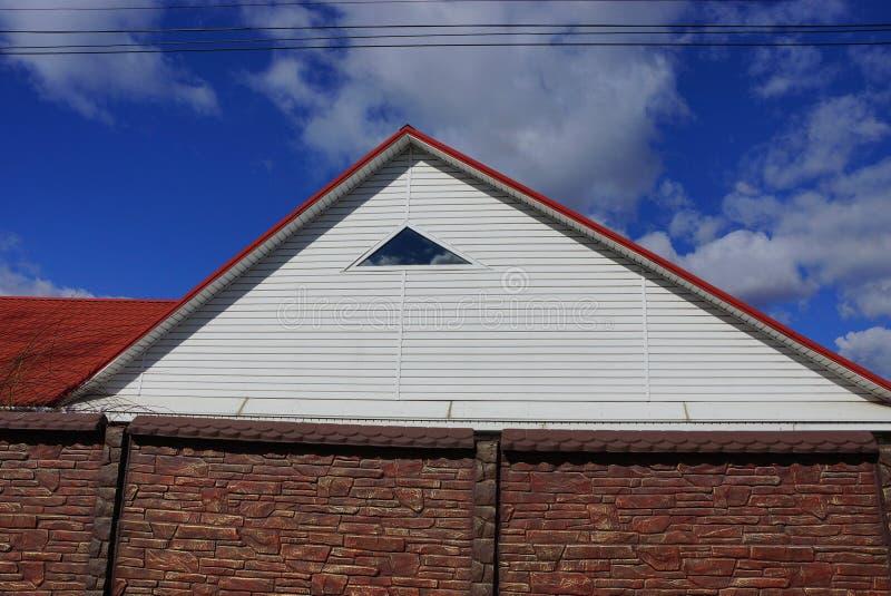 Een deel van het huis met een witte zolder met een klein venster onder een rood betegeld dak achter een steen bruine omheining stock foto's