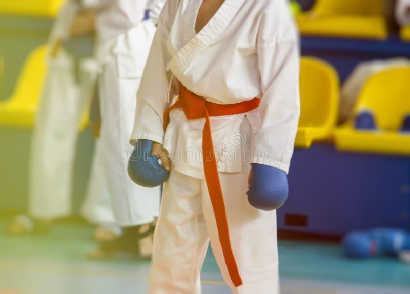 Een deel van het lichaam van een karatemens in kimono in handschoenen in de gymnastiek stock afbeelding
