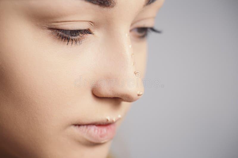 Een deel van jong vrouwengezicht met met dalingen van schoonheidsmiddel op de neus, mooi meisje die een samenstelling op studioac royalty-vrije stock foto's