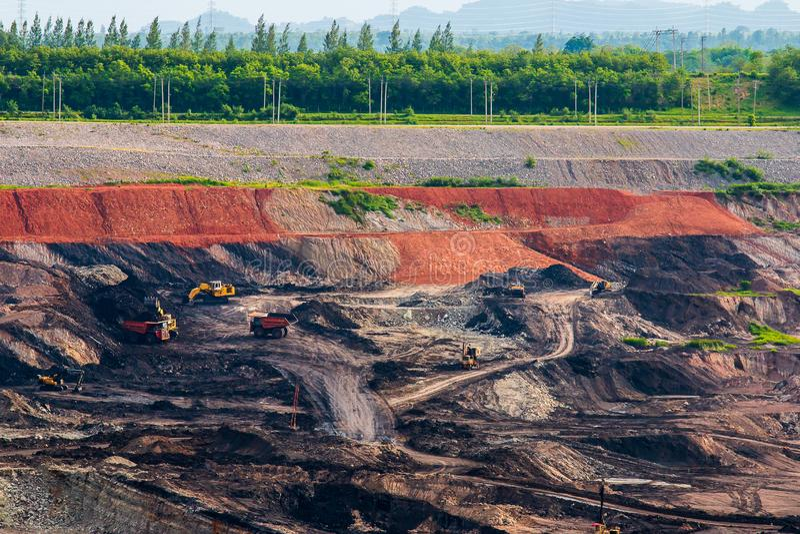 Een deel van een kuil met het grote mijnbouwvrachtwagen werken stock fotografie