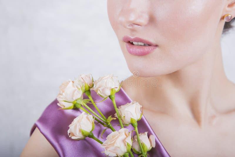 Een deel van mooi jong meisjes` s gezicht met romig rozenboeket stock foto's