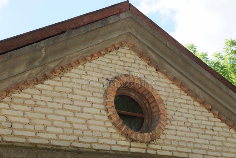 Een deel van een oude bruine baksteenzolder met een klein rond venster stock foto's