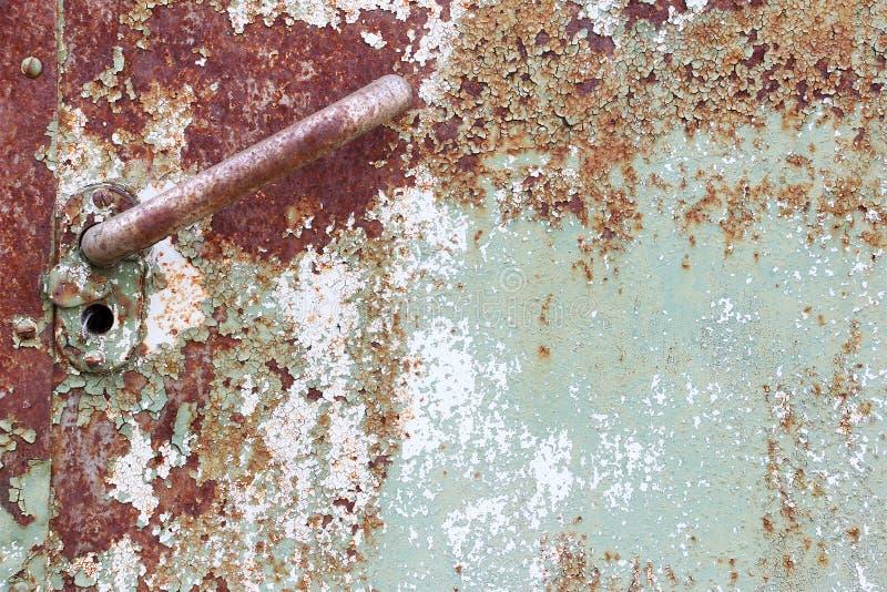 Een deel van oude roestige metaaldeur met handvat en sleutelgat, textuur stock afbeeldingen