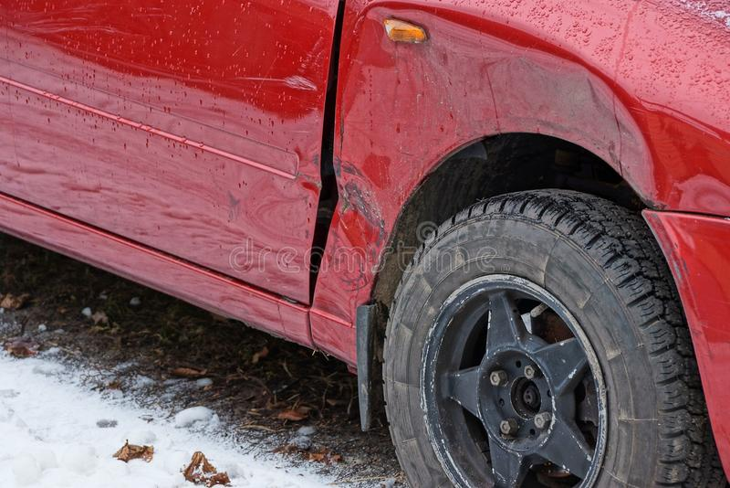 Een deel van een rode auto met een deuk in de vleugel en een zwarte rijden op de weg in de sneeuw stock foto