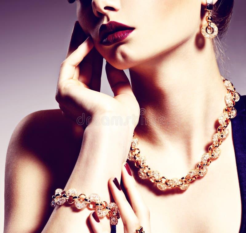 Een deel van vrouwelijk gezicht met mooie gouden juwelen op lichaam stock afbeeldingen