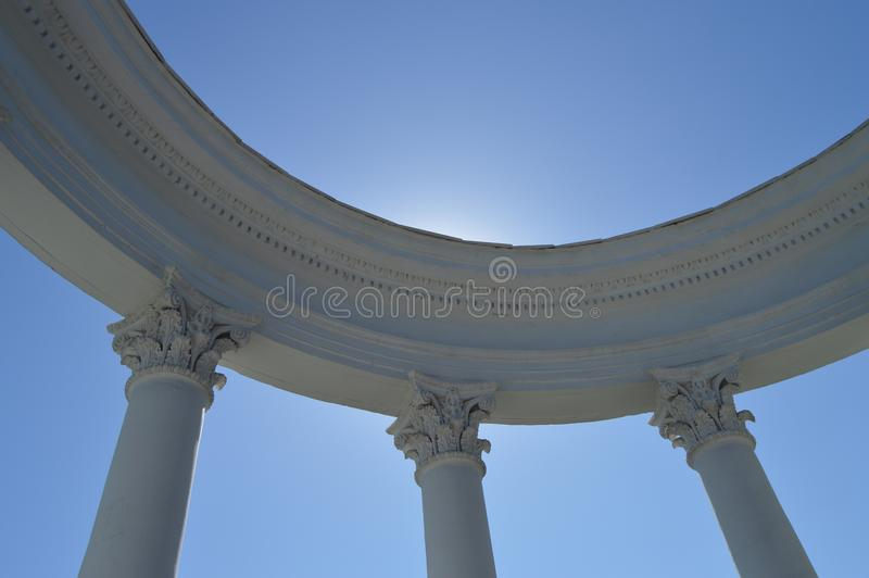 Een deel van een witte rotonde met kolommen tegen een blauwe hemel op een Zonnige dag royalty-vrije stock afbeeldingen