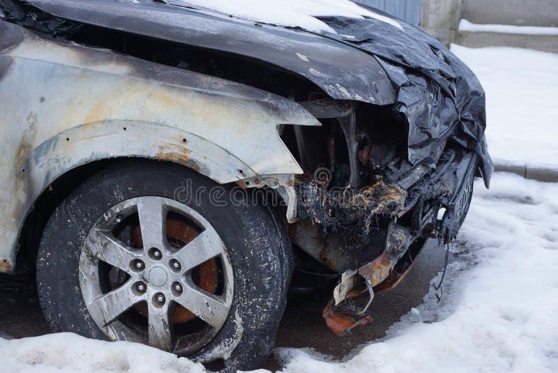 Een deel van een zwarte auto brandde in een neerstorting met een bumper en een wiel in de sneeuw op de straat royalty-vrije stock fotografie