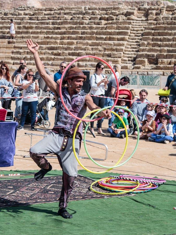 Een deelnemer van het Purim-festival jongleert met met hoepels voor bezoekers in Caesarea, Israël stock afbeeldingen