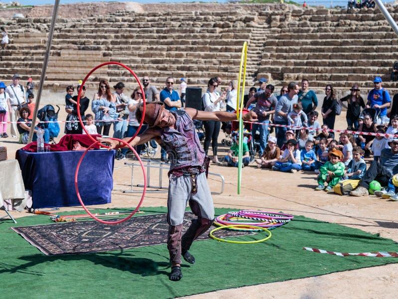Een deelnemer van het Purim-festival jongleert met met hoepels voor bezoekers in Caesarea, Israël royalty-vrije stock fotografie