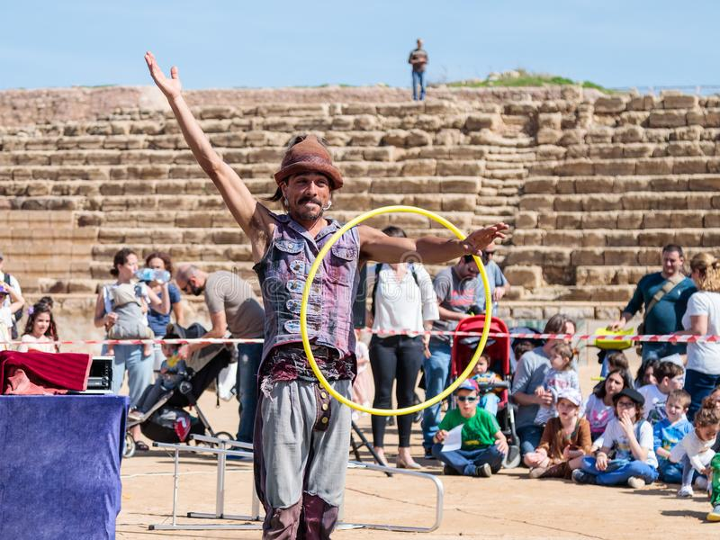 Een deelnemer van het Purim-festival jongleert met met hoepels voor bezoekers in Caesarea, Israël stock foto's