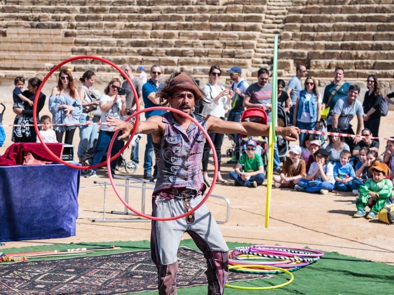 Een deelnemer van het Purim-festival jongleert met met hoepels voor bezoekers in Caesarea, Israël royalty-vrije stock afbeelding