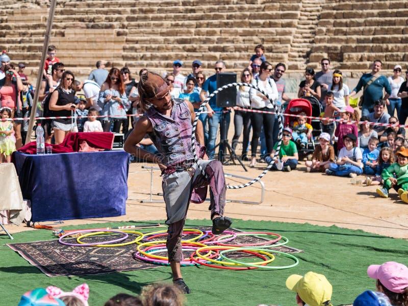 Een deelnemer van het Purim-festival jongleert met met hoepels voor bezoekers in Caesarea, Israël stock afbeelding