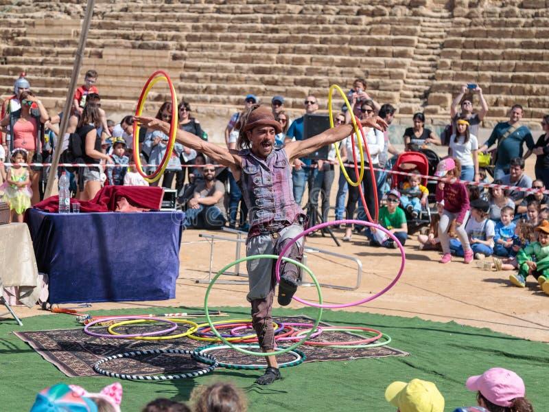 Een deelnemer van het Purim-festival jongleert met met hoepels voor bezoekers in Caesarea, Israël royalty-vrije stock foto