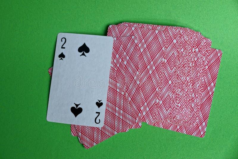 Een dek van rode kaarten met een piekdeuce op een groene lijst stock foto's