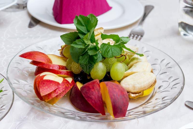Een dessert van appelen, bananen, druiven op een feestelijke lijst in een onderzoek royalty-vrije stock foto