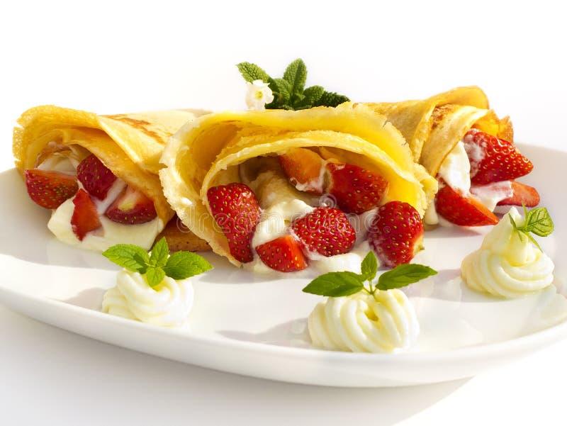 Een dessertplaat met pannekoeken, aardbei, slagroom en munt royalty-vrije stock foto's