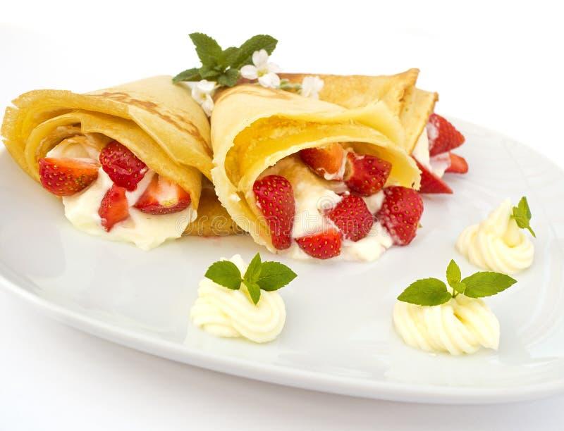 Een dessertplaat met pannekoeken, aardbei, slagroom en munt stock fotografie