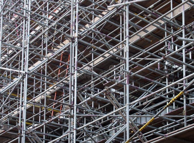 Een dicht netwerk van de polen van de metaalsteiger ondersteunend het werkplatforms op een bouwwerf stock afbeelding