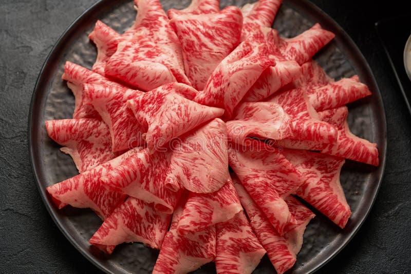 Een dicht omhooggaand gedetailleerd beeld van gesneden Japans wagyurundvlees in een ceramische die plaat op Shabu Shab wordt voor stock foto