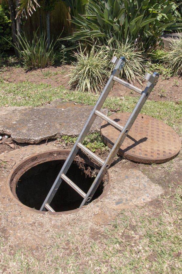 Een dichte eerlijke mening van een halve ladder van de metaalstrook uit plakkend een gat van de watermens met de dekking leidde t stock afbeeldingen