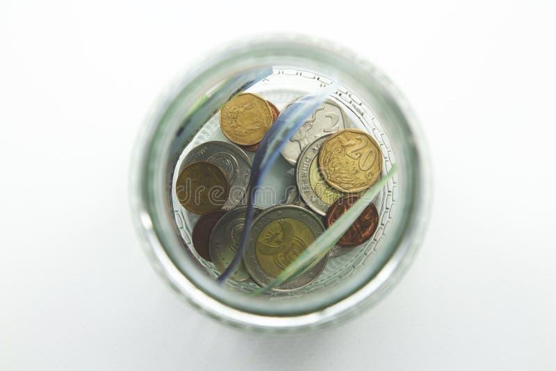 Een dichte omhooggaande foto van een hoogtepunt van de glaskruik van Zuidafrikaans geld met een duidelijke achtergrond stock foto's
