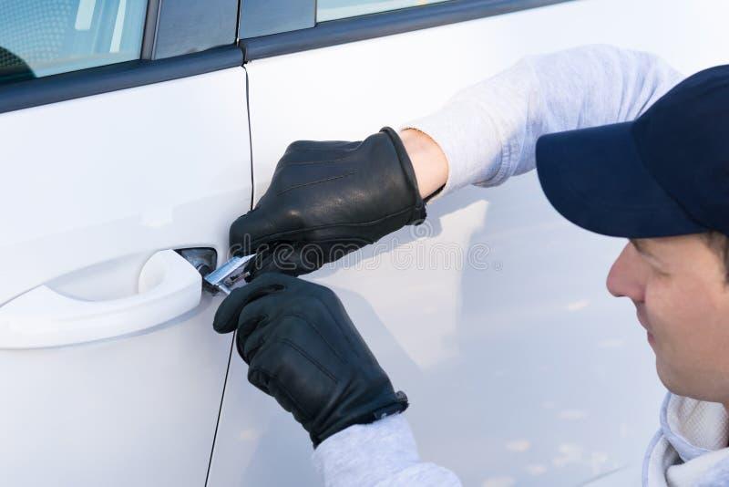 Een dief in een GLB wil het slot in de deur van een witte auto breken, close-up stock afbeelding