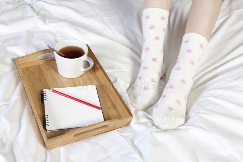 Een dienblad met een kop van koffie, een blocnote en een potlood bevindt zich op het bed stock foto