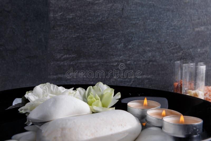 In een diepe kom met water is een kiezelsteen, aroma van kaarsen en knoppen van gekleurde bloemen stock afbeelding