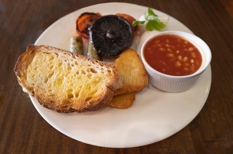 Een dik, gebukt stuk van het brondeegtoast met een vegetarisch ontbijt op een witte plaat royalty-vrije stock foto