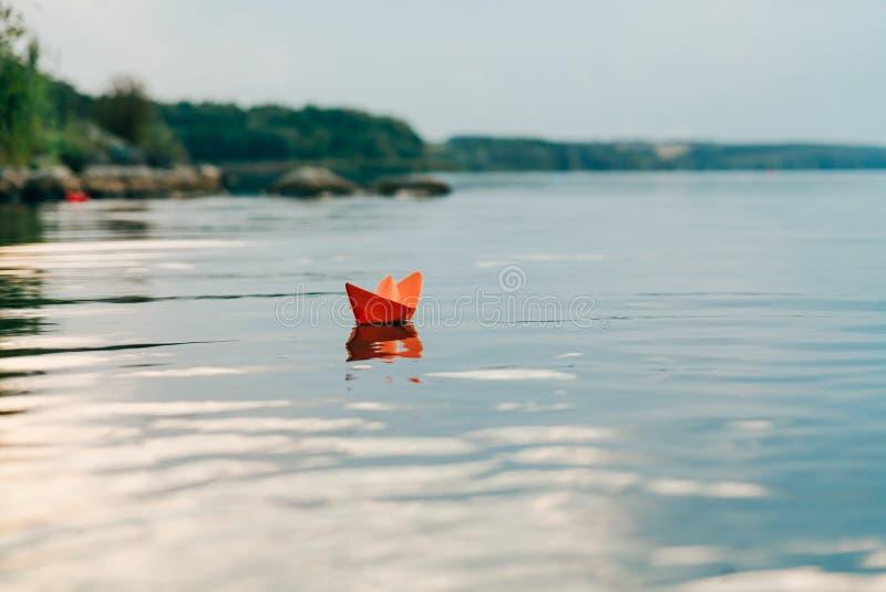 Een document bootzeilen door de rivier in de zomer Het heeft een oranje kleur en drijft stroomafwaarts langs de kust royalty-vrije stock foto's