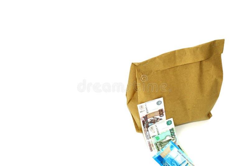 Een document zak met binnen voedsel Geld Op witte achtergrond stock foto's