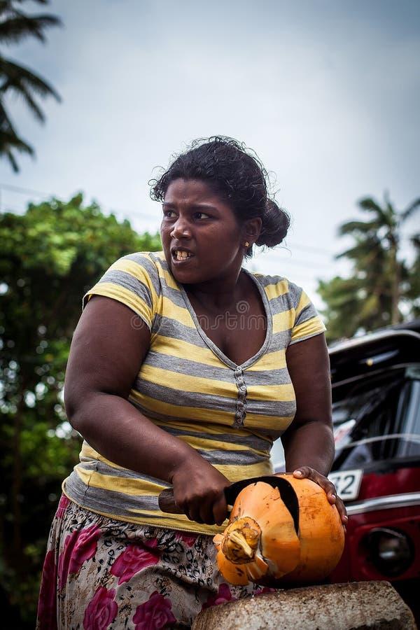 Een donker-gevilde vrouw snijdt een oranje kokosnoot met een groot mes Werkende harde vrouwen Sterke en waardige vrouw die hard w royalty-vrije stock foto's