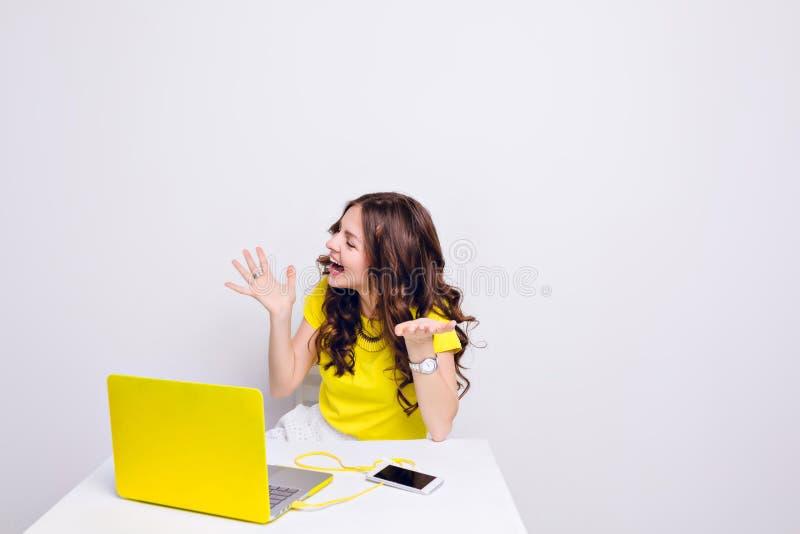 Een donkerbruin meisje met krullend haar speelt dwaas voor laptop in geel geval Zij zit achter witte lijst en stock afbeeldingen