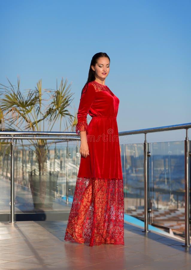 Een donkerbruine dame die zich op een balkon op een blauwe hemelachtergrond bevinden Een modieuze vrouw in een lange rode kleding stock foto's
