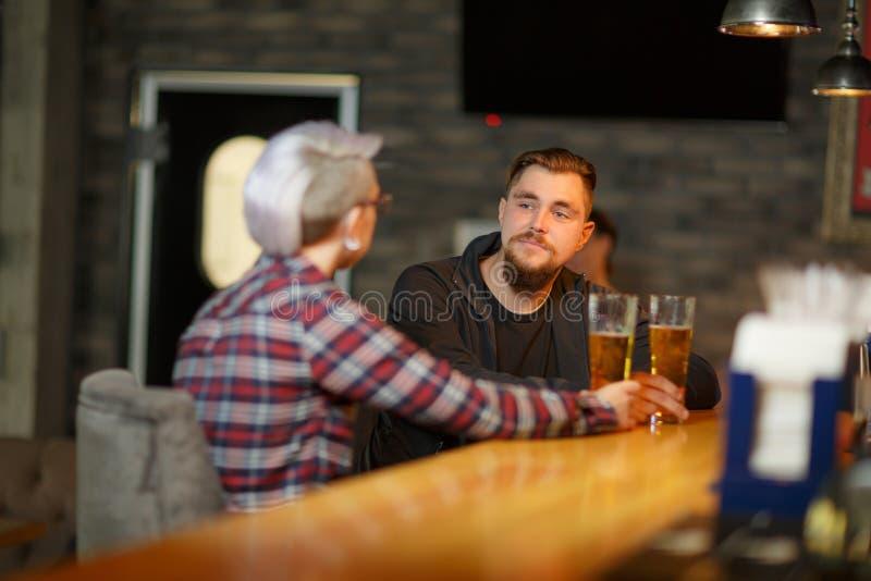 Een donkerbruine kerel met een baard, zit en spreekt in bar met een meisje en drinkt bier binnen stock afbeelding