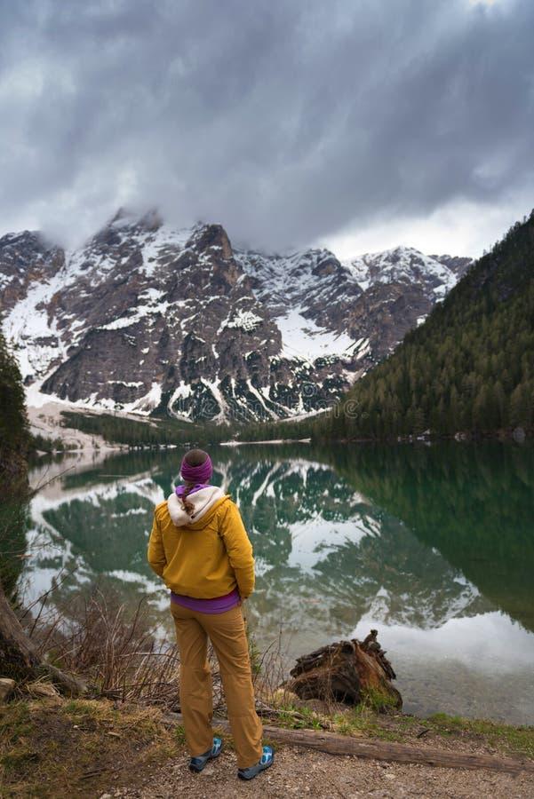 Een donkerbruine vrouwenwandelaar, die openluchttoestel dragen bevindt zich bekijkend uit de mening over Meer Braies stock foto's