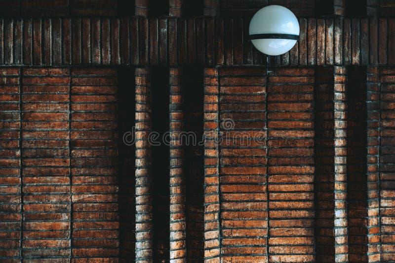 Een donkere bakstenen muur met een steenlamp royalty-vrije stock foto's