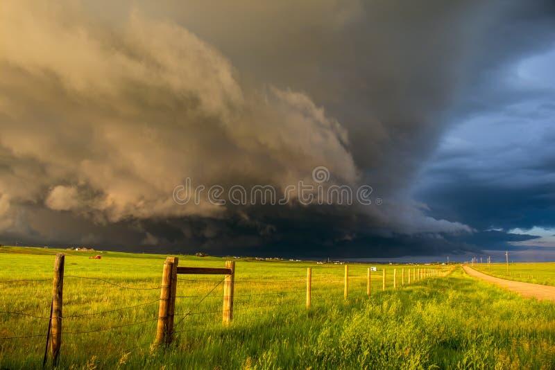 Een donkere van het plankenwolk en onweer benadering als zon glanst helder kijkend onderaan een omheining stock foto's