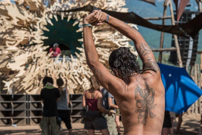 Een donkerharige met een tatoegering op zijn rug rekt zich bij het Verloren festival van de Theorie psytransce muziek uit royalty-vrije stock foto's