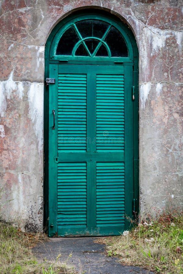 Een doorstane concrete openlucht ondergrondse kelder met groene houten deur stock afbeeldingen