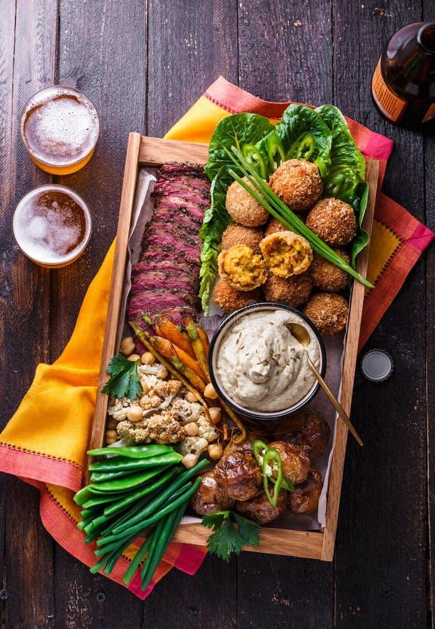Een doos met falafel, vlees, geassorteerde groenten en onderdompeling Arabische stijl Hoogste mening royalty-vrije stock fotografie