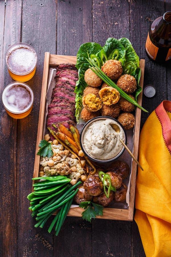Een doos met falafel, vlees, geassorteerde groenten en onderdompeling Arabische stijl Hoogste mening royalty-vrije stock foto's