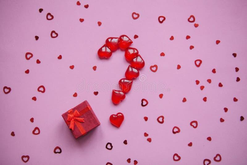 Een doos met een gift en een aantal vraagtekens die van kleine rode harten worden opgemaakt stock afbeeldingen