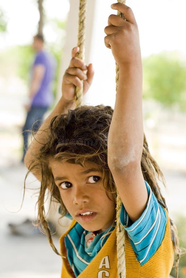 Een dorpsjongen die met een schommeling speelt stock foto